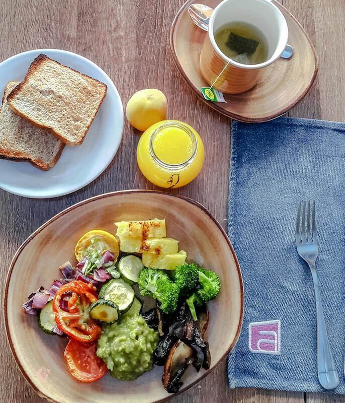 pan, taza con te, vegetales y jugo de naranja