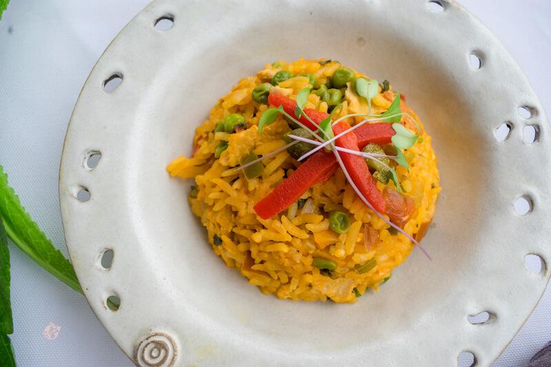plato blanco con arroz con pollo vegano, decorado con pimiento morron