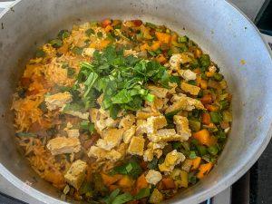 foto de una olla con arroz, pollo vegano y vegetales dentro,