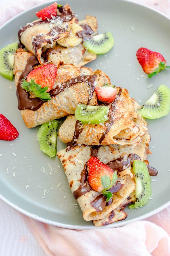 crepes veganos en un plato verde menta decorado con fresas y kiwis y salsa de chocolate