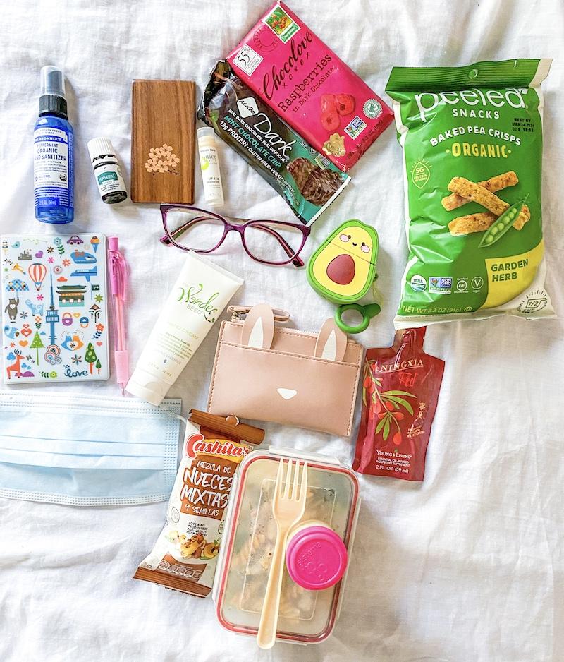 foto con productos sobre fondo blanco: pasaporte, billetera rosada, lentes morados, boligrafo, crema de manos, aguacate. Articulos para viajar vegano en tiempos de COVID