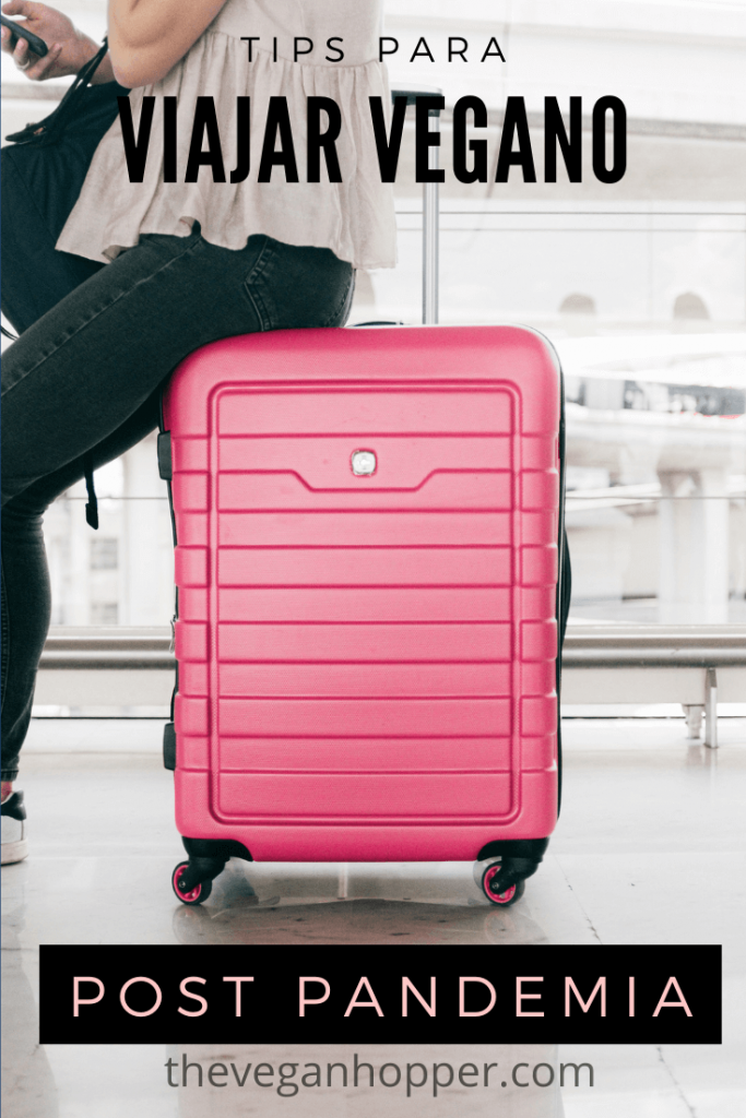 Tips para viajar vegano post COVID- mujer sentada sobre maleta rosada