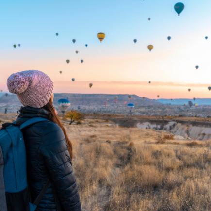 mujer de espalda y globlos en el cielo-viajar vegano post covid